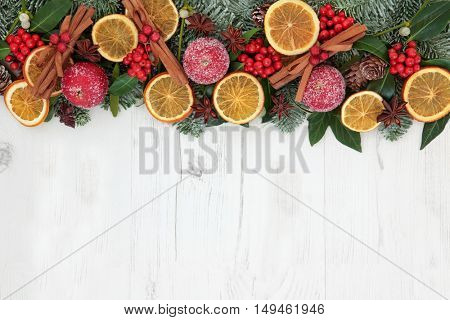 Christmas dried fruit abstract background border with orange slices, spices, apple decorations, holly, ivy, mistletoe, and snow covered spruce fir over distressed white wood background.