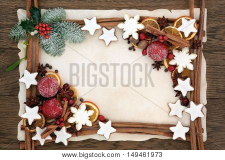 Christmas abstract background border with gingerbread biscuits, cinnamon sticks, spices, dried orange, apple and cranberry fruit with holly, fir and mistletoe on parchment paper over oak wood.