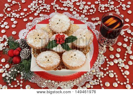 Christmas mince pie cakes with mulled wine, holly, baubles, winter greenery and silver decorations on red background.