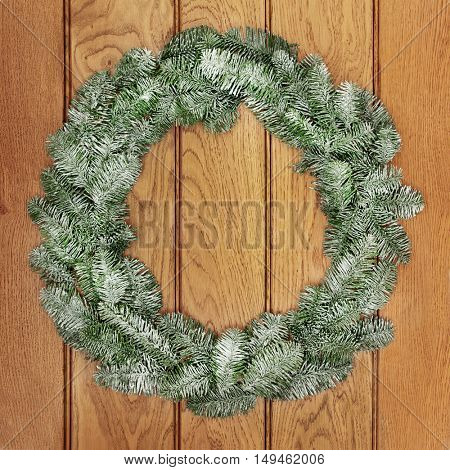 Christmas snow covered blue spruce fir wreath decoration on oak front door background.