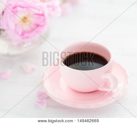 Cup of coffee and  bouquet of roses on rustic table. . Selective focus. Shallow depth of field.