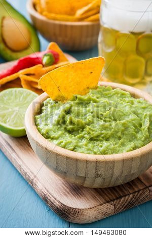 Nachos, guacamole and ingredients on blue wooden table