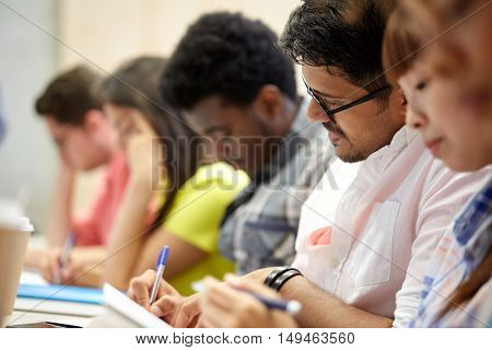 education, high school, university, learning and people concept - group of international students writing at lecture