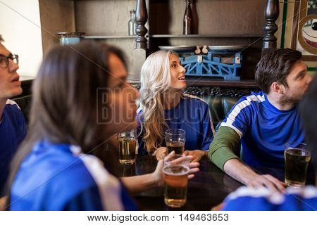 people, leisure and sport concept - worried friends or football fans drinking beer and watching soccer game or match at bar or pub