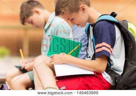 primary education, friendship, childhood, communication and people concept - elementary school student boys with backpacks writing to notebooks and sitting on bench outdoors