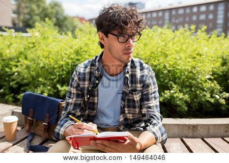 lifestyle, creativity, freelance, inspiration and people concept - creative man with notebook or diary writing sitting on city street bench