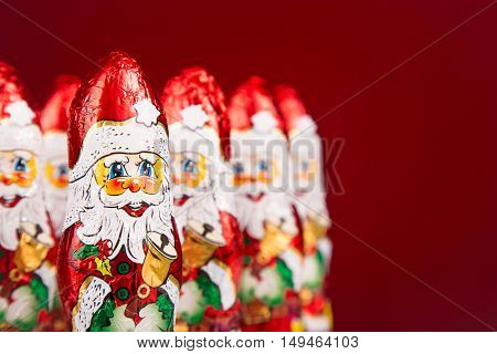 Close-up of Santa Claus chocolate figurine on red background