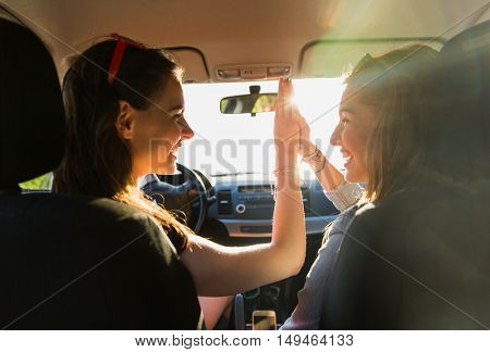 summer vacation, holidays, travel, road trip and people concept - happy teenage girls or young women driving in car and making high five gesture