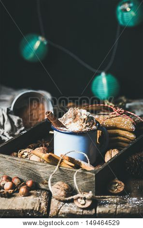 Mug of hot chocolate with whipped cream, cocoa powder, cinnamon, gingerbread cookies, nuts in wooden tray, dark wall with Christmas decoration garland of blue balls at background, selective focus