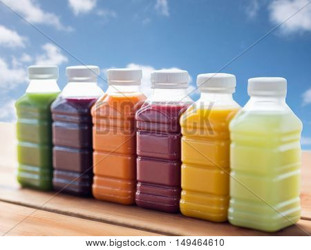 healthy eating, drinks, dieting and packaging concept - plastic bottles with different fruit or vegetable juices on wooden table over blue sky background
