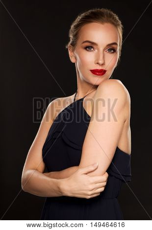 people, luxury and fashion concept - beautiful woman in black with red lips over dark background