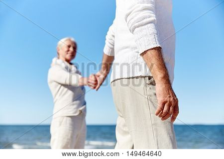 family, age, travel, tourism and people concept - close up of happy senior couple holding hands on summer beach