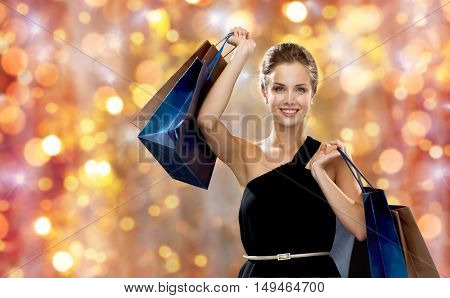 sale, people, christmas and holidays concept - smiling woman in dress with shopping bags over lights background