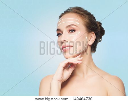 beauty, people, plastic surgery, anti-age and health concept - beautiful young woman touching her face over blue background