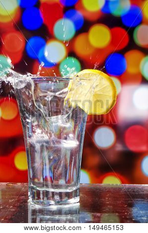 the refreshing water with ice and splashes on a bright background