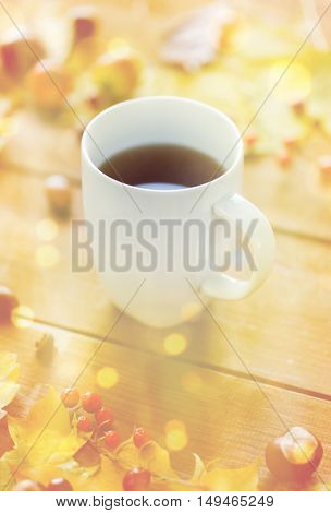 season, drink and morning concept - close up of tea cup on wooden table with autumn leaves
