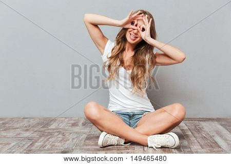 Portrait of a funny young girl looking at camera through fingers while sitting on the floor isolated on a gray background