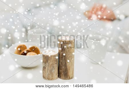 christmas, winter, holidays and concept - close up of candles, cookies and tea cups on table over family couple on background