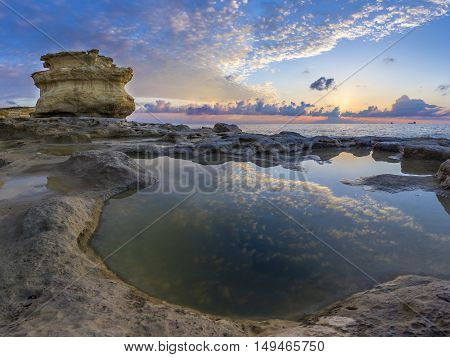Malta - Sunrise at St.Peter's Pool with huge rocks of Delimara and reflections of the sky and clouds