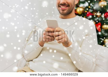 christmas, technology, people and holidays concept - close up of smiling man with smartphone at home