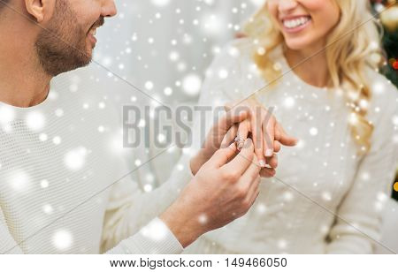 love, couple, relationship and holidays concept - happy man giving diamond ring to woman for christmas
