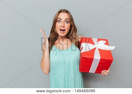 Happy surpised young woman standing and holding gift box over gray background