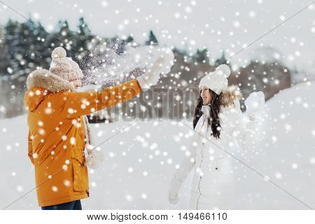 people, season, love and leisure concept - happy couple playing with snow in winter