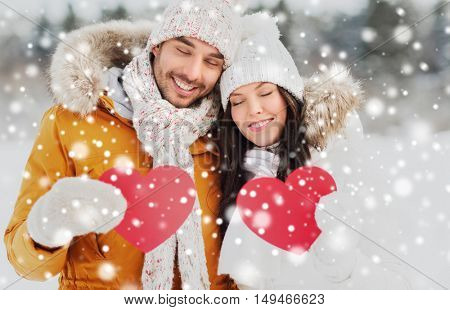 people, season, love and valentines day concept - happy couple holding blank red hearts over winter landscape
