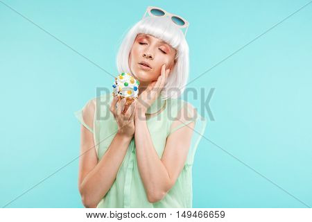 Portrait of attractive sensual blonde young woman with cupcake over blue background