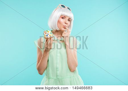 Happy playful young woman in blonde wig tasting cupcake by finger over blue background