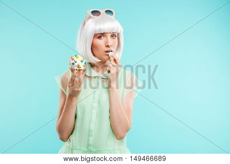 Beautiful young woman in blonde wig standing and eating cupcake over blue background