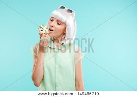 Happy lovely young woman in blonde wig eating cupcake over blue background
