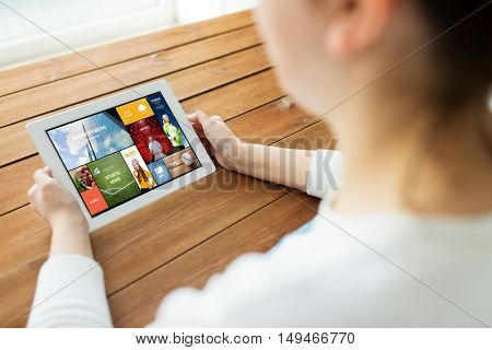 technology, people and advertisement concept - close up of woman with internet news on tablet pc computer screen on wooden table