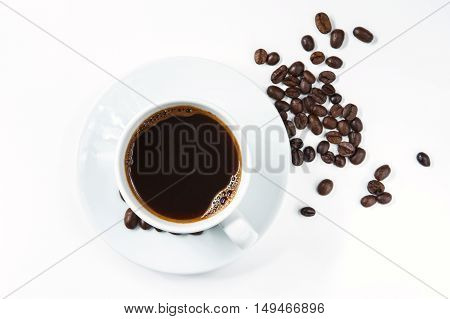 Cup of coffee with coffee beans on white background. Top view.