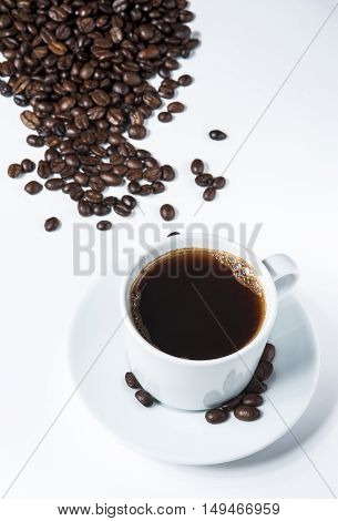 Cup of coffee with heap of coffee beans on white background. Top view.