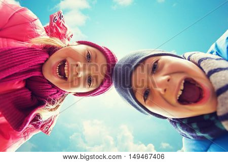 childhood, leisure, friendship, autumn and people concept - happy boy and girl faces outdoors over blue sky and clouds background