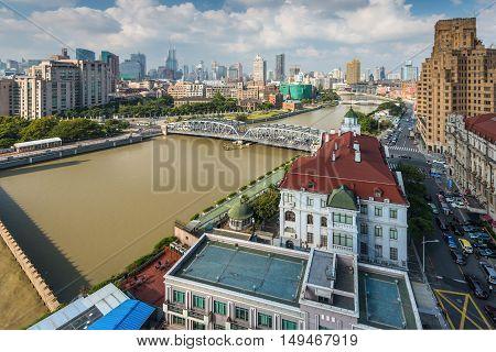 Shanghai China - October 23 2013: Cityscape Suzhou Creek old iron Waibaidu Bridge (Garden Bridge) and the Russian Consulate in the foreground Shanghai China.