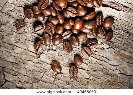 Coffee beans on a wooden background close up