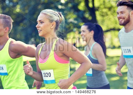 fitness, sport, friendship, race and healthy lifestyle concept - group of happy teenage friends or sportsmen running marathon with badge numbers outdoors