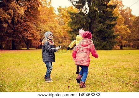 autumn, childhood, leisure and people concept - group of happy little kids playing tag game and having fun in park outdoors