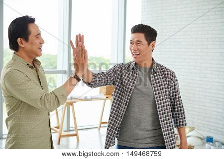 Adult Asian man giving high five to his coworker
