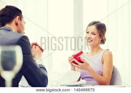 restaurant, couple and holiday concept - excited young woman looking at boyfriend with gift box at restaurant