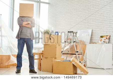Start-up project manager standing with cardboard box on his head