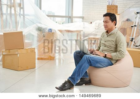Vietnamese businessman sitting in beanbag and working on laptop