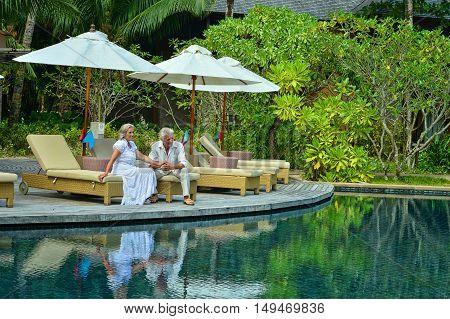 Senior couple relaxing near pool at hotel resort