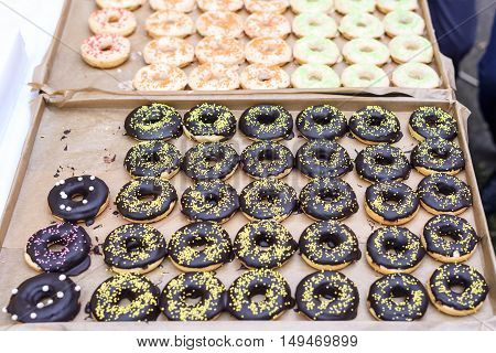 Chocolate donuts, yellow, red, orange, pink and green sugar on top, shallow focus