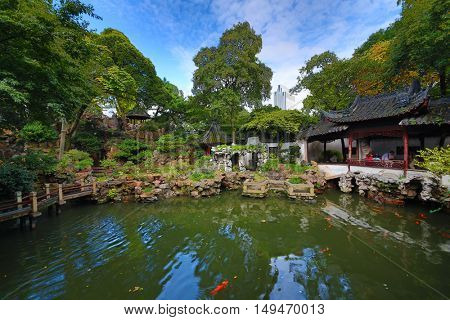 Beautiful pond and old buildings in China garden, walking tourists, HDR