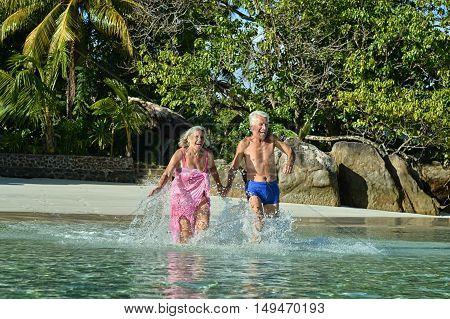 Happy elderly couple running on a beach