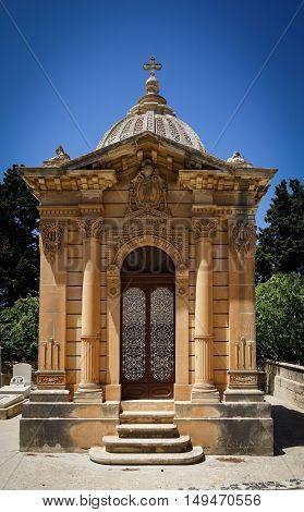 The old single family crypt on a blue sky background. Santa Marija Addolorata cemetery. Paola. Malta.