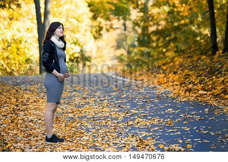 young pregnant girl walks in autumn forest
